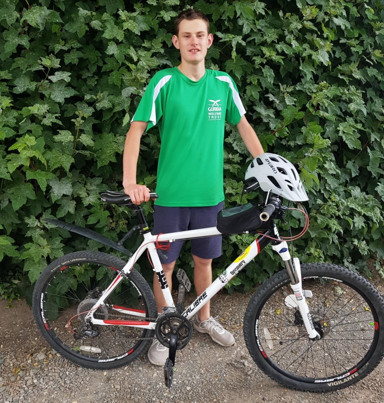 Photo of Jools Brennan and his bike with a hedge in the background